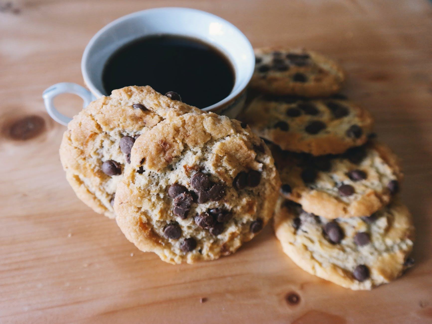 half dozen chocolate chip cookies on wooden table with black coffee in a cup